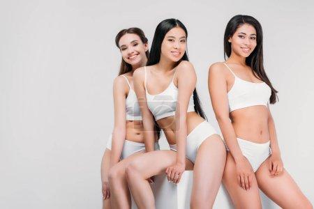 Foto de Atractivas chicas multiétnicas en ropa interior posando en cubo blanco, aislado en gris - Imagen libre de derechos