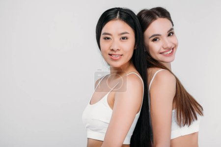 attractive smiling multiethnic girls in white bras looking at camera, isolated on grey
