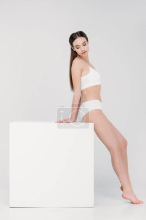 beautiful tender girl in underwear posing near white cube, isolated on grey