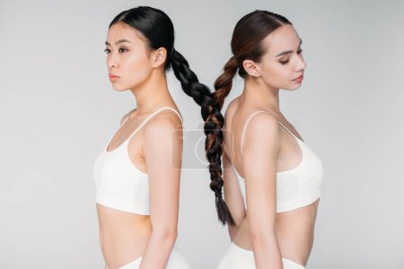 Photo for Attractive multiethnic girls with hair in one braid, isolated on grey - Royalty Free Image