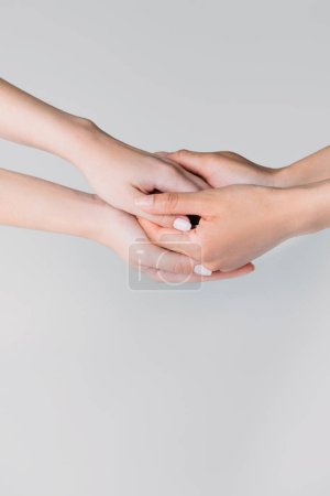 partial view of girls holding hands, isolated on grey