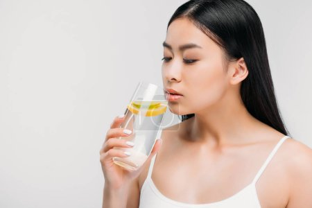 charming asian girl drinking pure water with lemon, isolated on grey