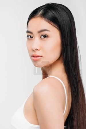 attractive asian girl looking at camera, isolated on grey