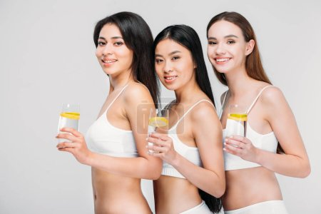 beautiful smiling multiethnic girls holding glasses with lemon water, isolated on grey, healthy lifestyle