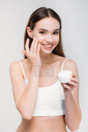 elegant smiling girl applying face cream, isolated on grey