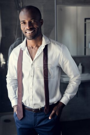 smiling young businessman in white shirt with tie hanging on shoulders at bathroom