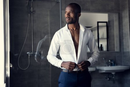 thoughtful businessman buttoning his white shirt at bathroom and looking away