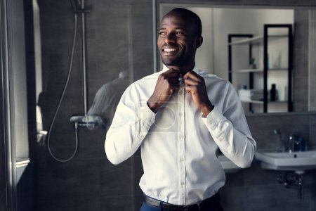 smiling businessman buttoning his white shirt at bathroom and looking away