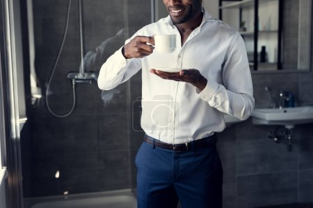 handsome young businessman in white shirt drinking coffee at bathroom