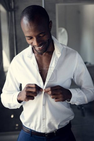 happy young businessman buttoning his white shirt before work