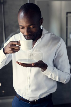 handsome young businessman in white shirt enjoying cup of coffee