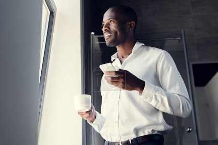 bottom view of happy young businessman in white shirt using smartphone during coffee break