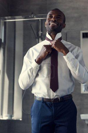 Photo pour Vue de dessous du beau jeune homme d'affaires en chemise blanche mise sur sa cravate à la salle de bain - image libre de droit