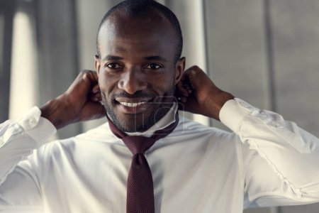 happy young businessman in white shirt putting on his tie
