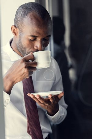 handsome young businessman enjoying delicious cup of coffee