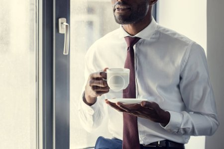 cropped shot of young businessman with cup of coffee in front of window
