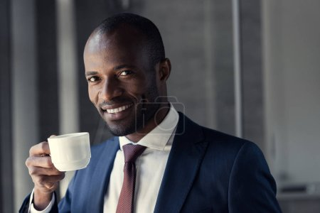 smiling young businessman with cup of coffee looking at camera