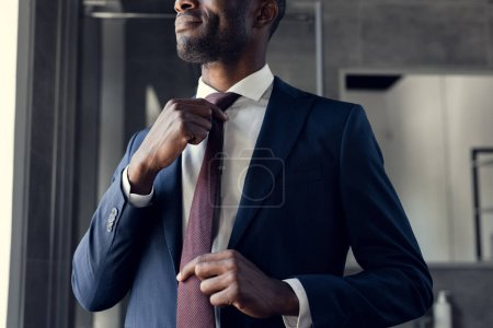 plan recadré de jeune homme d'affaires mettant sa cravate à la salle de bain