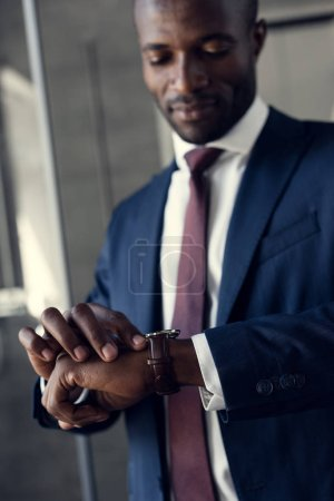 close-up portrait of handsome young businessman in stylish suit looking at wristwatch