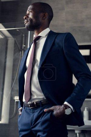 Photo pour Jeune homme d'affaires en costume élégant, debout dans la salle de bain et en regardant loin - image libre de droit
