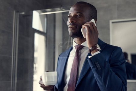stylish young businessman with cup of coffee talking by phone