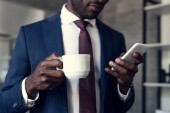 cropped shot of handsome young businessman with cup of coffee using smartphone