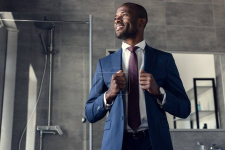 handsome young businessman in stylish suit standing in bathroom and looking away