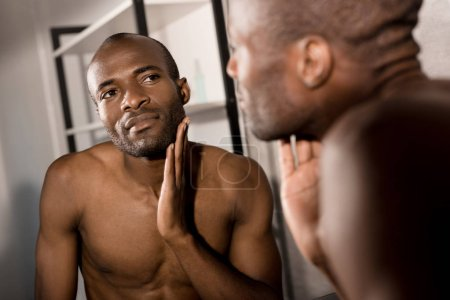 close-up shot of attractive young man examining clarity of skin while looking at mirror in bathroom