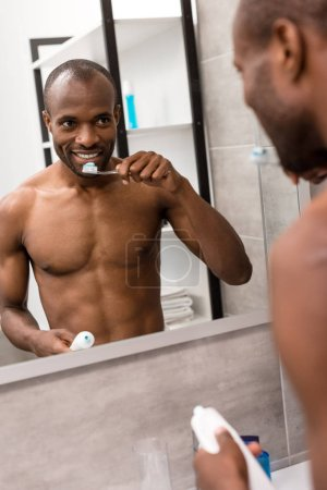 happy young man brushing teeth while looking at mirror in bathroom in morning