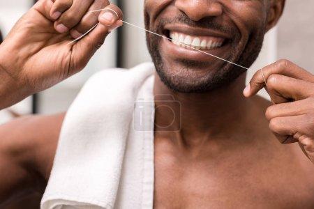 Photo pour Recadrée tir du jeune homme, nettoyer les dents avec la soie dentaire - image libre de droit