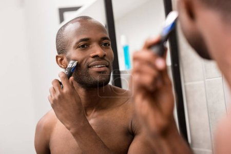 happy young man shaving beard with electric shaver while looking at mirror in bathroom