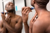 african american young man shaving beard with electric shaver while looking at mirror in bathroom