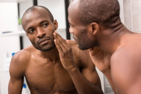 handsome young man examining clarity of skin while looking at mirror in bathroom