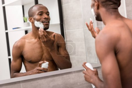 attractive young man applying shaving gel while looking at mirror in bathroom