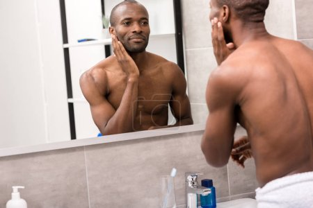 handsome young man applying facial lotion after shaving while looking at mirror in bathroom
