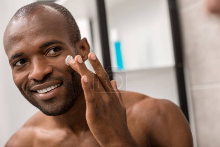happy young man applying facial cream while looking at mirror in bathroom