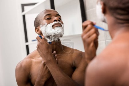 handsome african american man shaving with foam and razor and looking at mirror