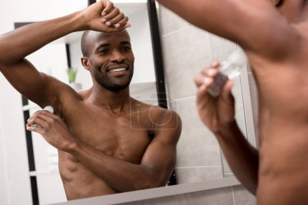 smiling bare-chested african american man applying antiperspirant in bathroom
