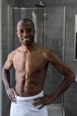 handsome bare-chested african american man in towel standing with hands on waist and smiling at camera in bathroom