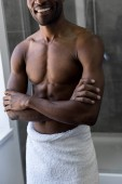 cropped shot of smiling shirtless african american man in towel standing with crossed arms in bathroom