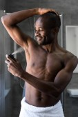 smiling shirtless african american man in towel holding deodorant spray in bathroom