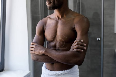 cropped shot of smiling african american man in towel standing with crossed arms in bathroom