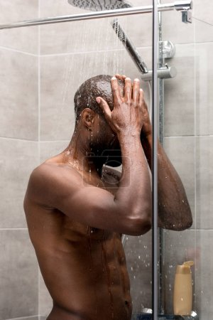 side view of young bare-chested african american man standing and washing body in shower