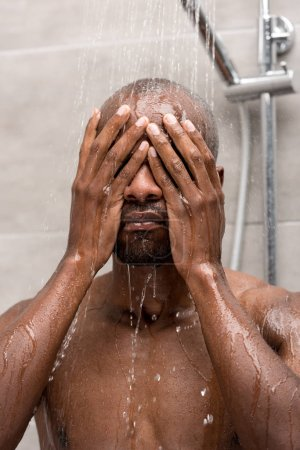 young african american man washing face and body in shower