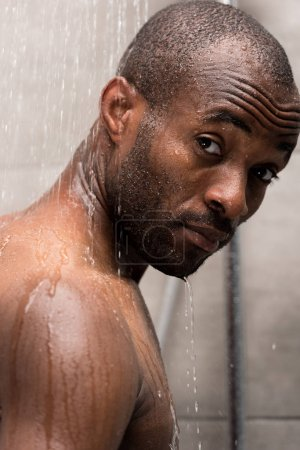 close-up view of young african american man washing in shower and looking at camera