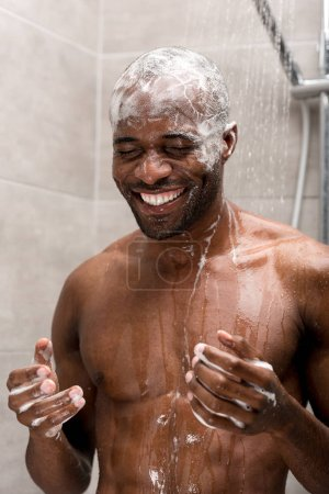 Photo pour Smiling young african american man washing head with shampoo in shower - image libre de droit