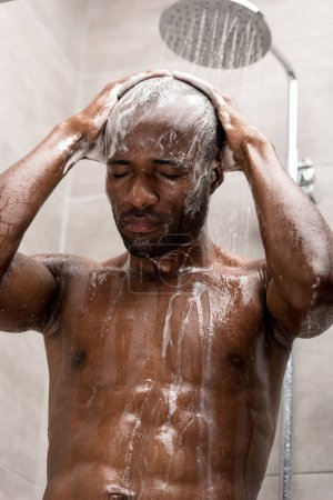 young african american man washing head with shampoo in shower
