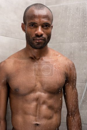 handsome young bare-chested african american man looking at camera while standing in shower