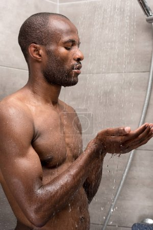 Photo pour Handsome young african american man standing and washing in shower - image libre de droit