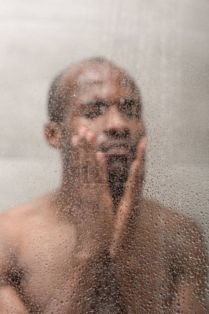 selective focus of handsome young african american man washing in shower